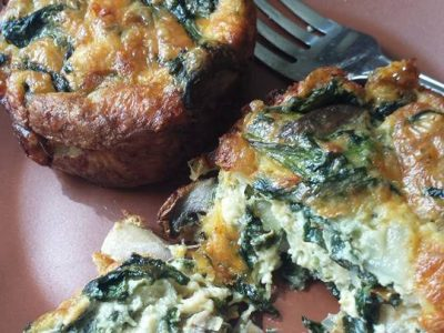 close-up photo of two spinach mushroom crustless mini quiches, one split open with a stainless steel fork behind it on a plate