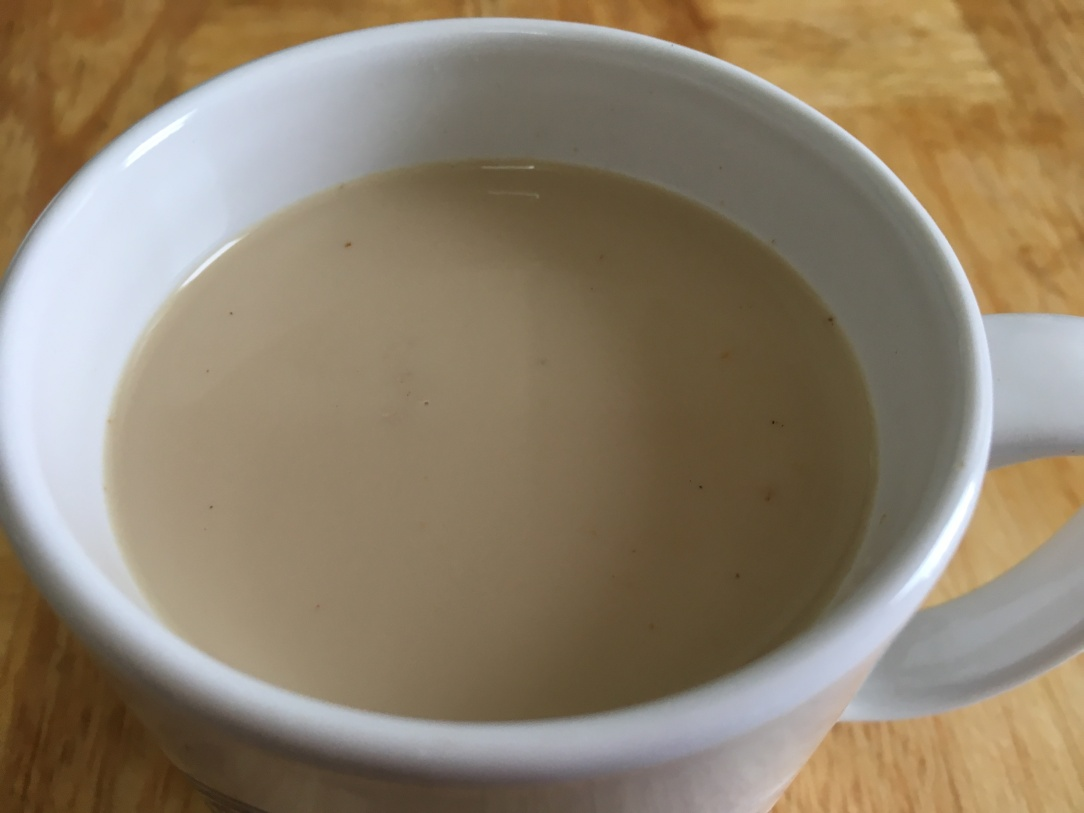 close-up photo of masala chai in a white mug on a wood surface