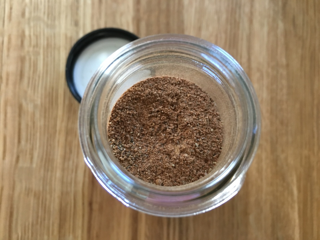 close-up top-down photo of chai spice in an open glass spice jar on a wooden counter