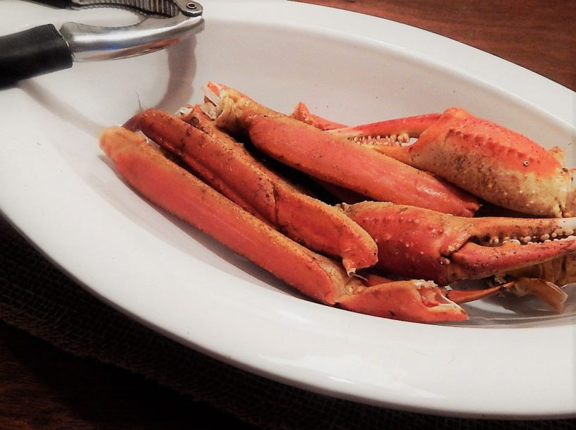 close-up photo of steamed crab legs in an oval white bowl with a seafood cracker