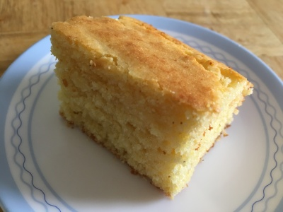 close-up photo of a square of sweet cornbread on a small white plate with blue trim on a wooden surface