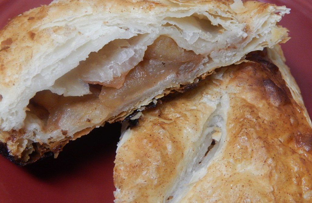 apple turnover, split in half, on a red plate