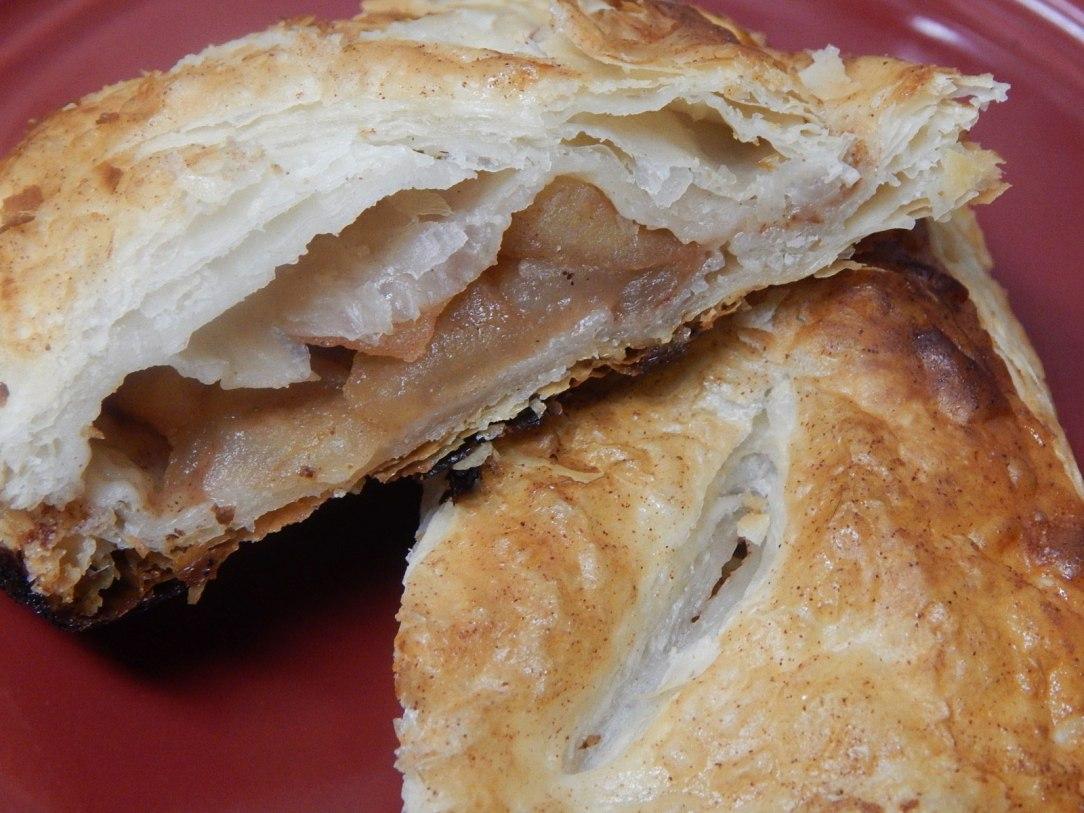 close-up photo of a split apple turnover on a red plate