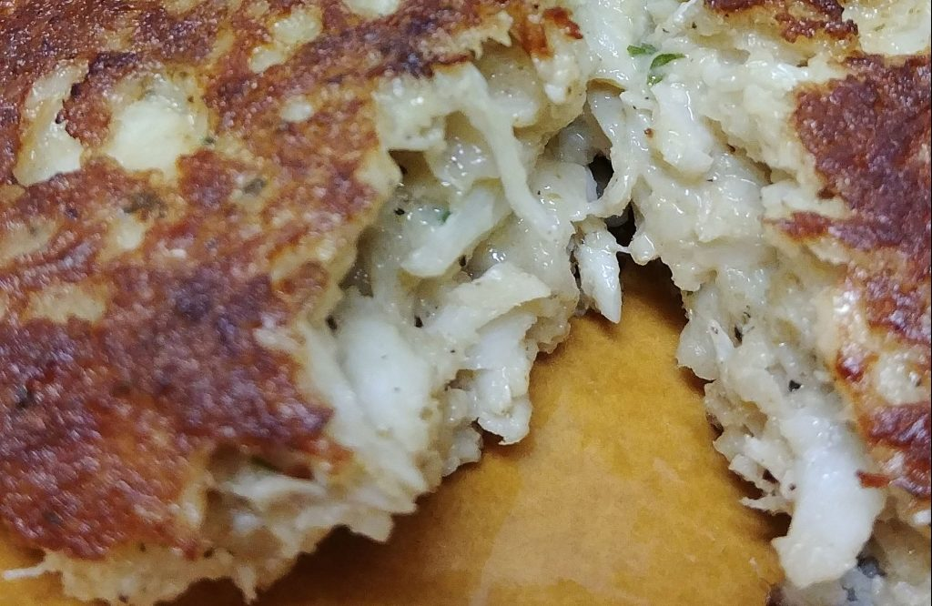 a crab cake split in half on a yellow plate
