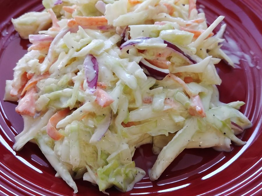 close-up photo of creamy coleslaw on a red plate