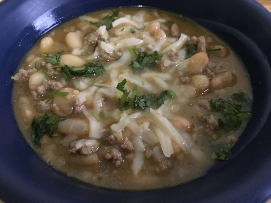 close-up photo of white chili in a cobalt blue bowl on a wooden surface