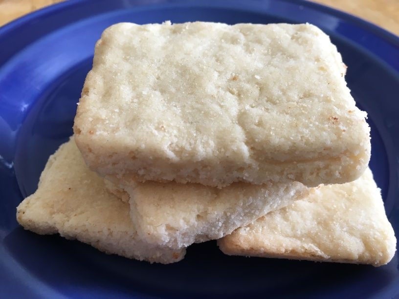 close-up photo of four pieces of shortbread on a small cobalt blue plate on a wooden surface
