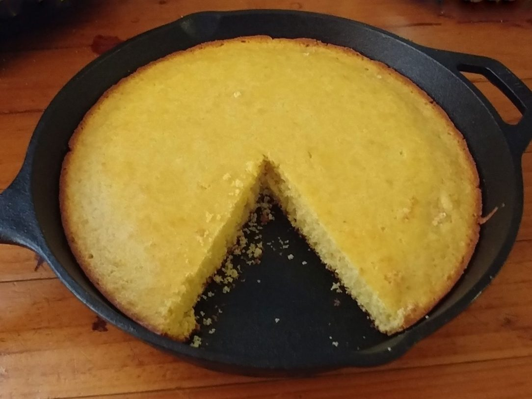 close-up photo of sweet cornbread, with a slice removed, in a cast-iron skillet on a wooden surface
