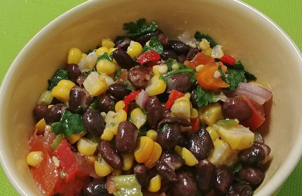 corn and black bean salad with garlic lime dressing in a bowl on a green surface