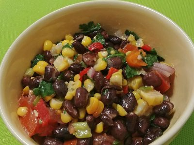 close-up photo of corn and black bean salad with garlic lime dressing in a bowl on a green surface