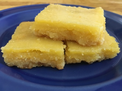 close-up photo of three lemon bar squares on a small cobalt blue plate on a wooden surface