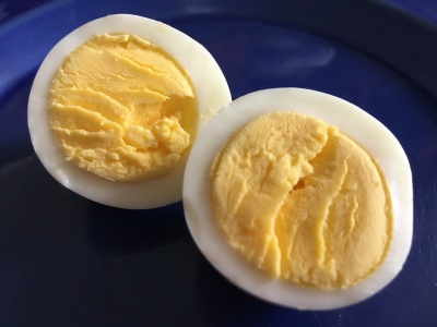 close-up photo of a hard-boiled egg sliced in half on a small cobalt blue plate