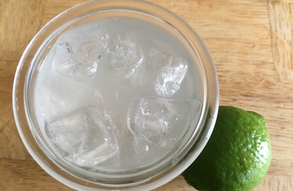limeade with ice in a glass next to a whole lime on a wooden surface
