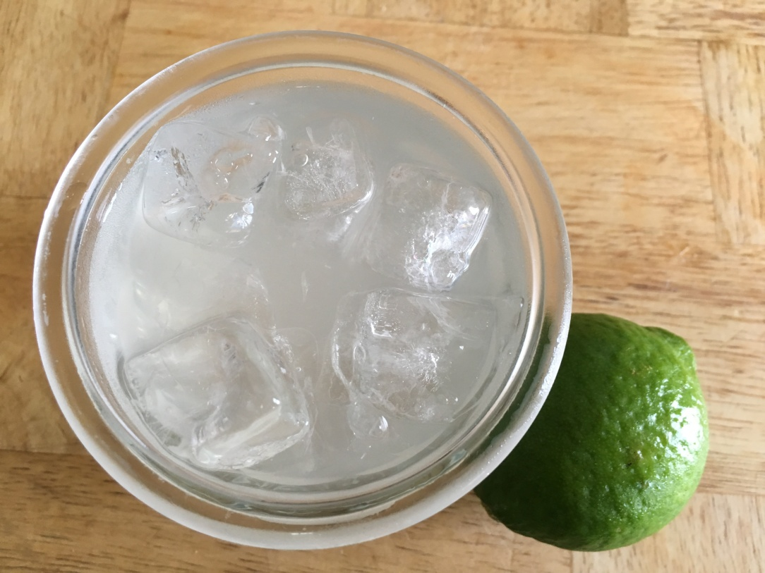 close-up photo of limeade with ice in a glass next to a whole lime on a wooden surface