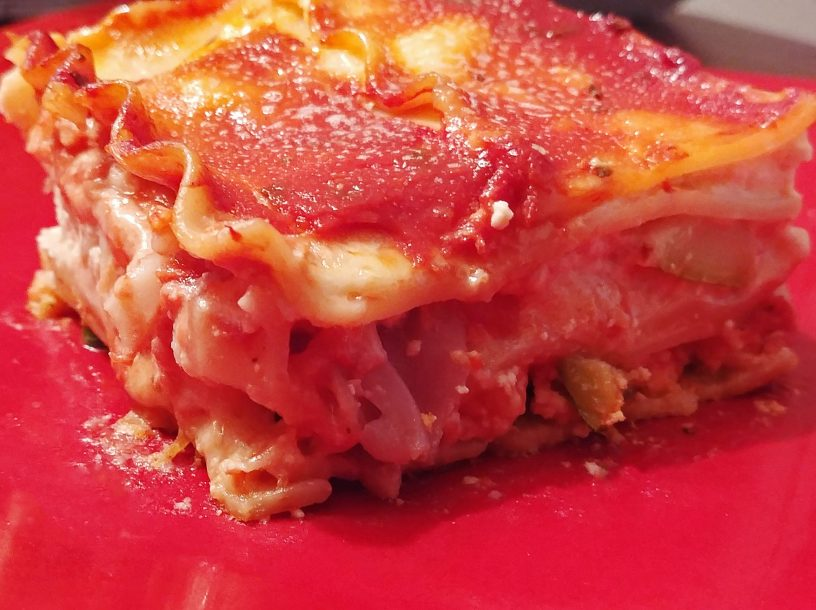 close-up photo of vegetable lasagna on a red plate
