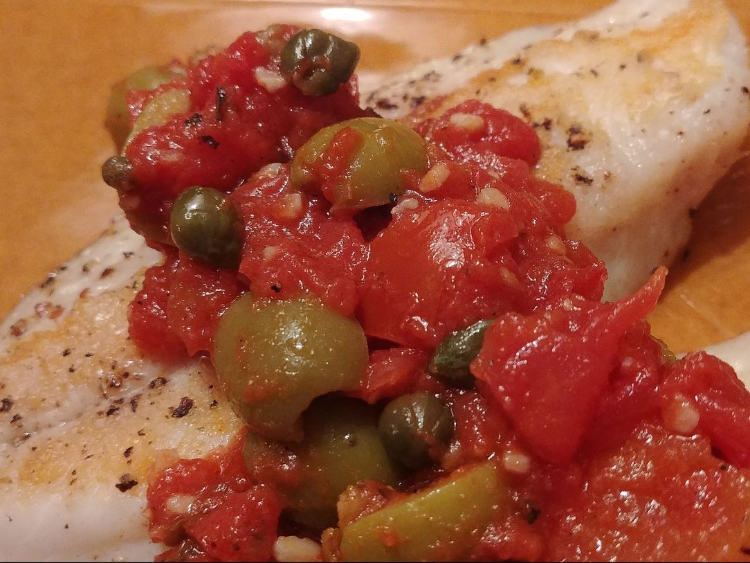 close-up photo of snapper with tomatoes, olives, and capers on a yellow plate
