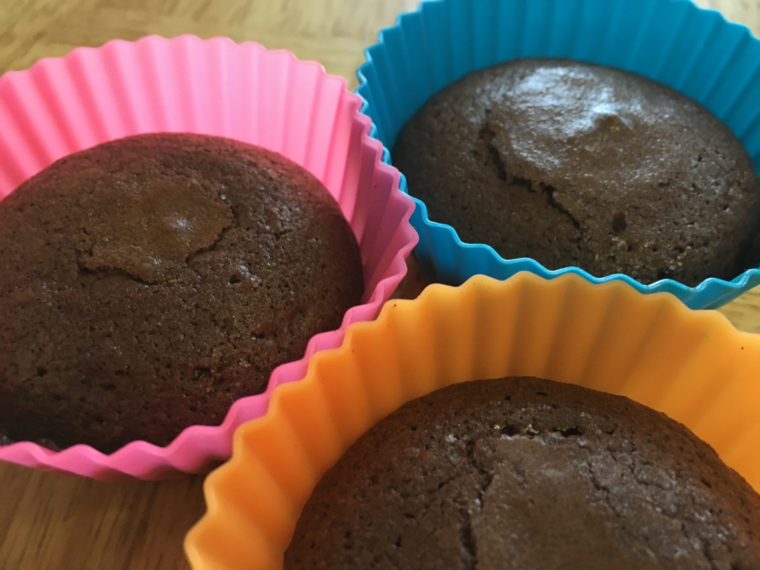 close-up photo of three brownies in colorful silicone muffin cups on a wooden surface