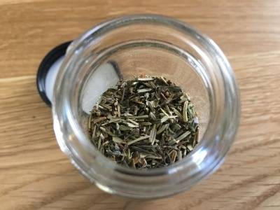 close-up top-down photo of herbes de Provence in an open glass spice jar on a wooden counter