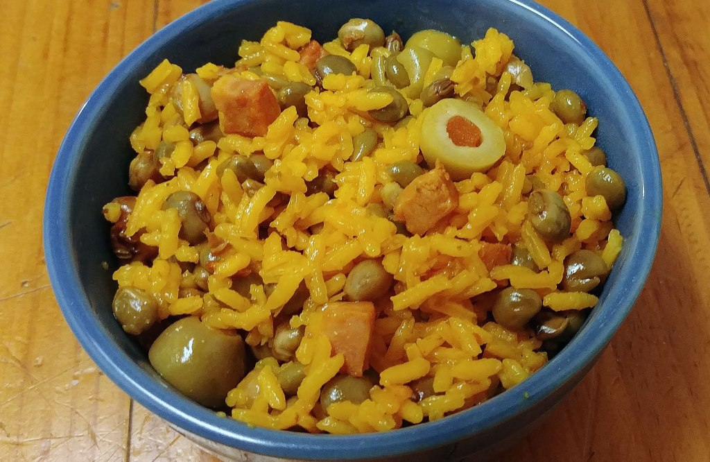 Spanish rice with pigeon peas (arroz con gandules) in a blue bowl on a wooden counter