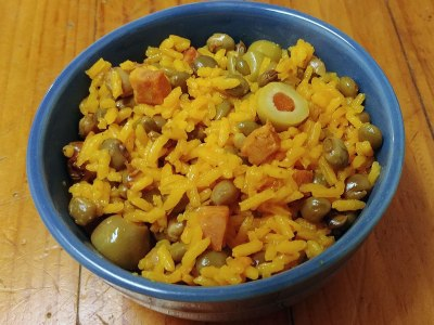 close-up photo of Spanish rice with pigeon peas (arroz con gandules) in a blue bowl on a wooden counter