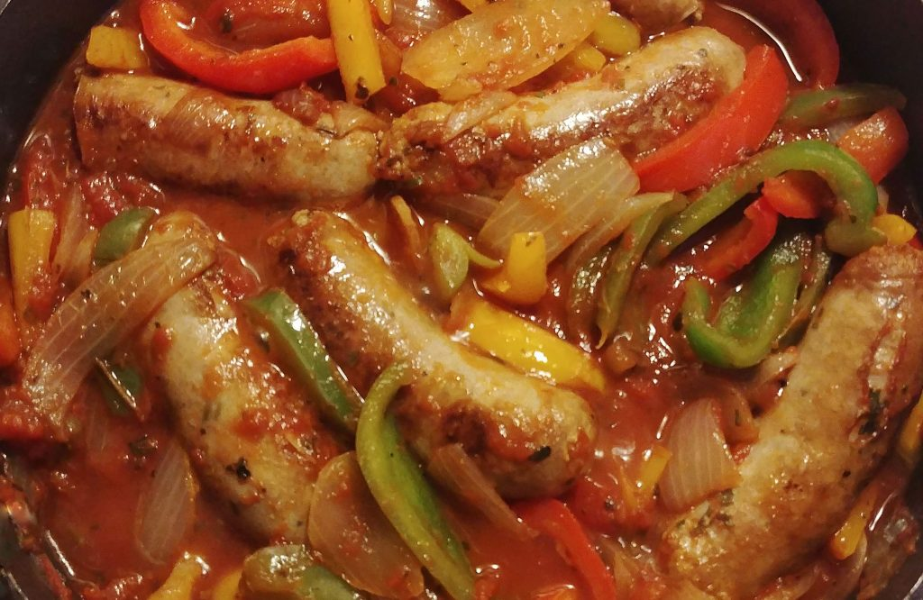 sausage and peppers in a cast-iron skillet