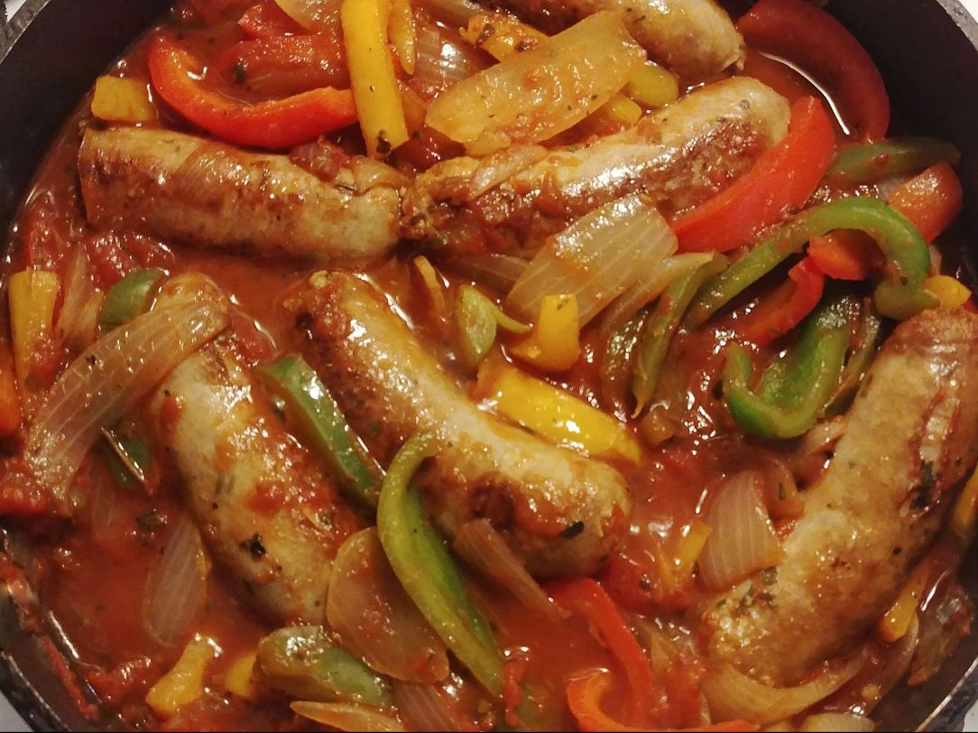 close-up top-down photo of sausage and peppers in a cast-iron skillet