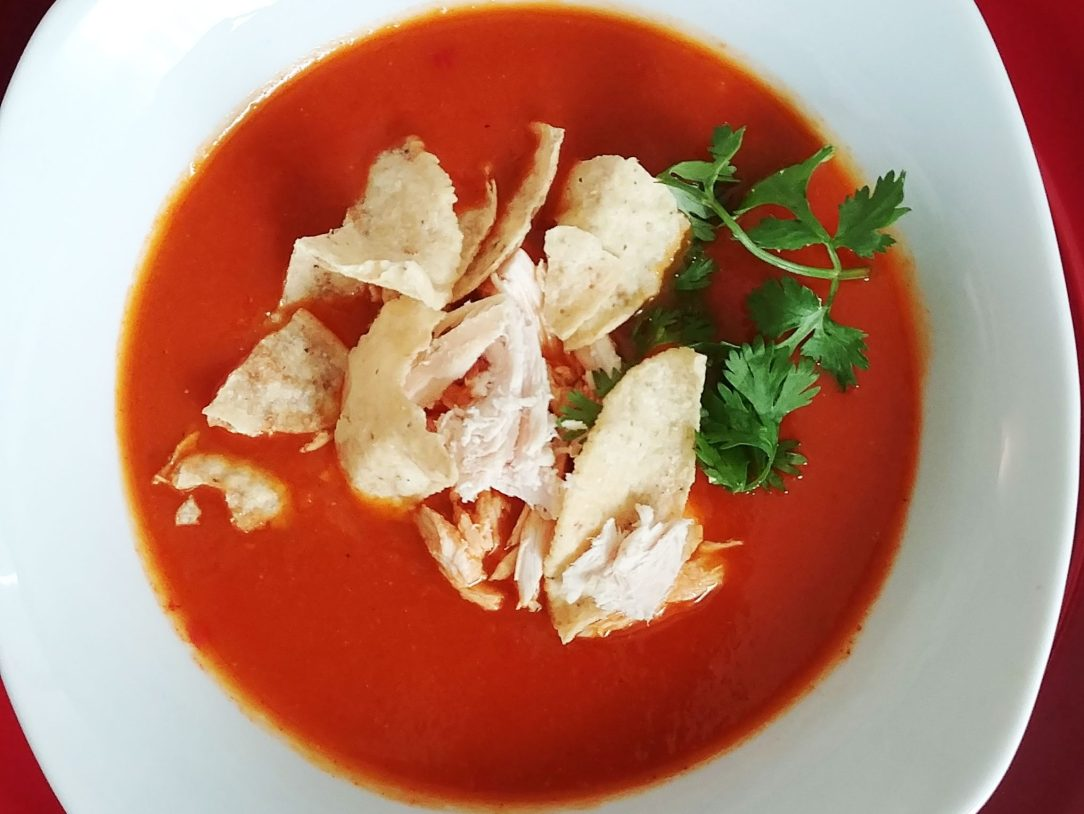 chicken tortilla soup garnished with cilantro in a white bowl