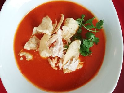 close-up top-down photo of chicken tortilla soup garnished with cilantro in a white bowl