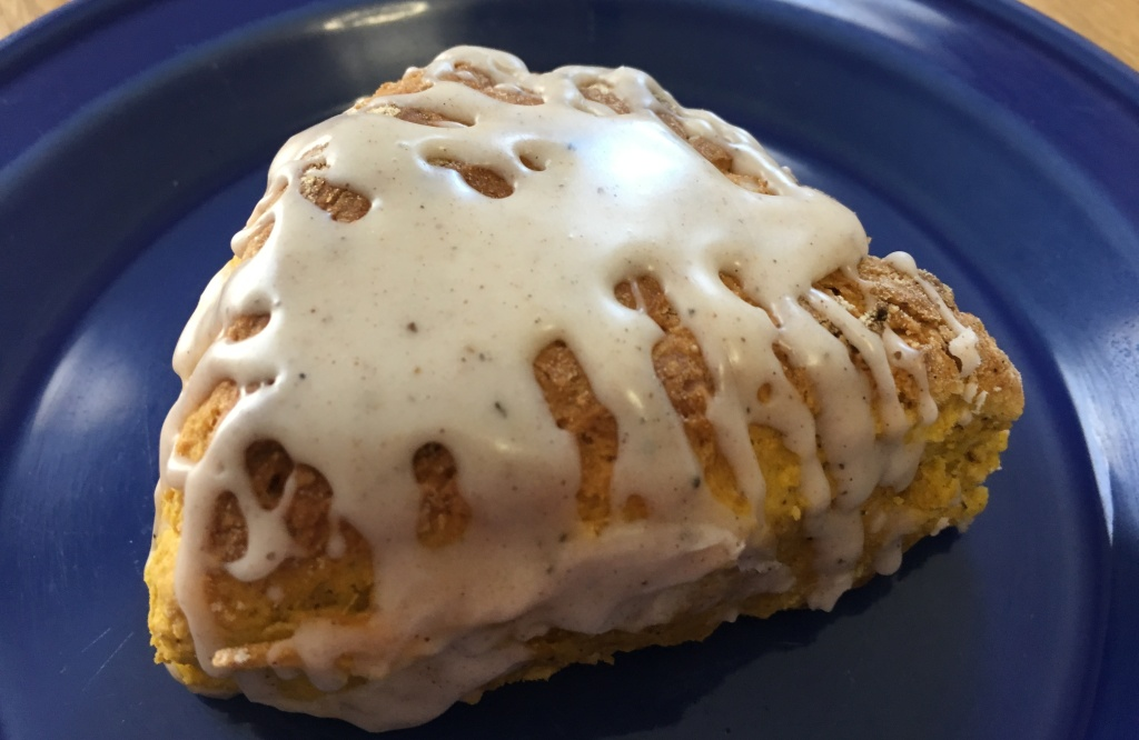 pumpkin scone with chai spice glaze on a small cobalt blue plate on a wooden surface