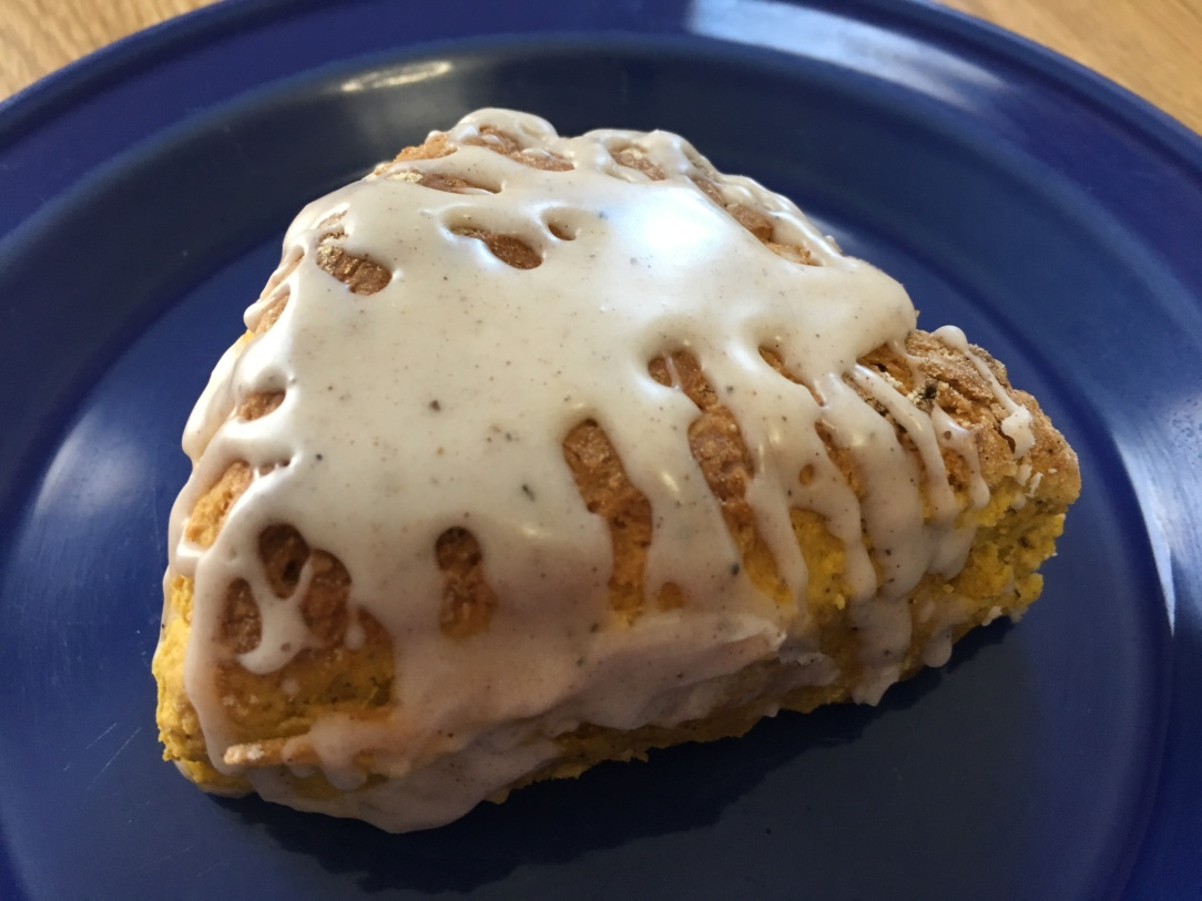 close-up photo of a pumpkin scone with chai spice glaze on a small cobalt blue plate on a wooden surface