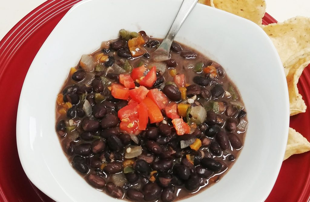 Black bean soup garnished with diced tomatoes in a white bowl on a red plate with tortilla chips on the side. There is a stainless steel spoon in the bowl.