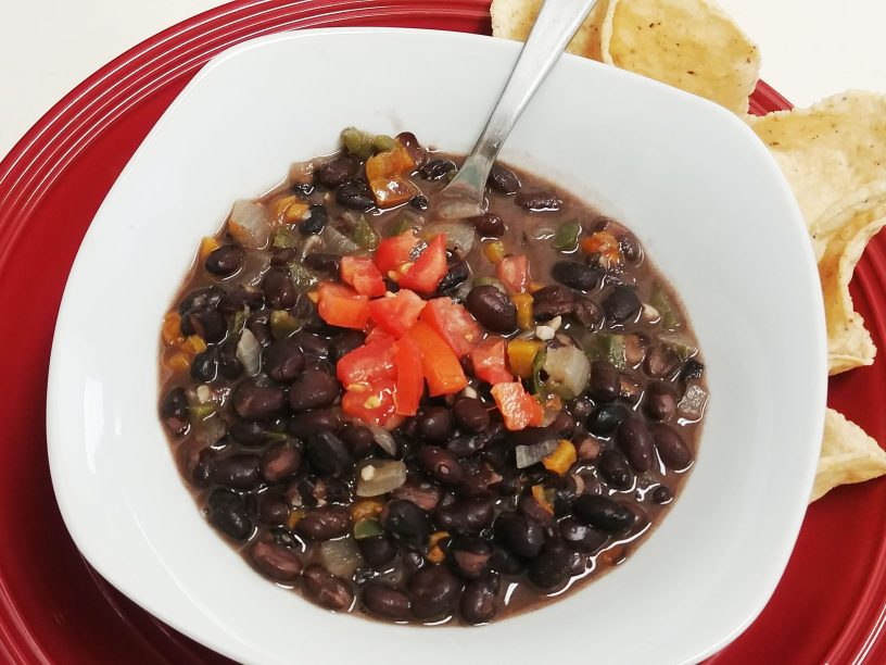 close-up photo of a stainless steel spoon in black bean soup garnished with diced tomatoes in a white bowl on a red platter with tortilla chips on the side