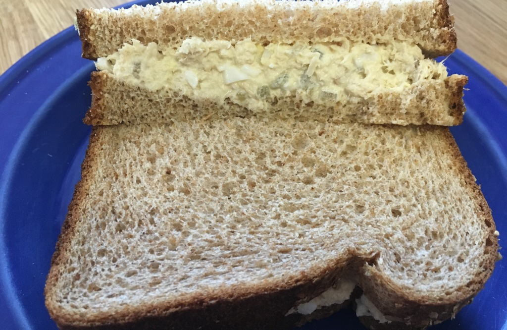 sliced whole wheat tuna salad sandwich on small cobalt blue plate on wooden surface