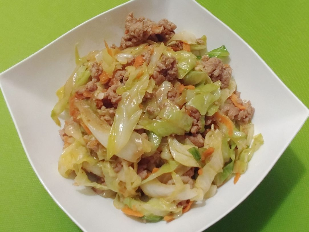 close-up photo of pork and cabbage stir-fry in a square (oriented as a diamond) white bowl on a lime green surface