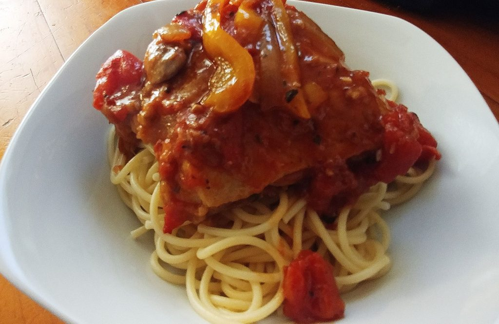 chicken cacciatore over spaghetti in a white plate on a wooden counter