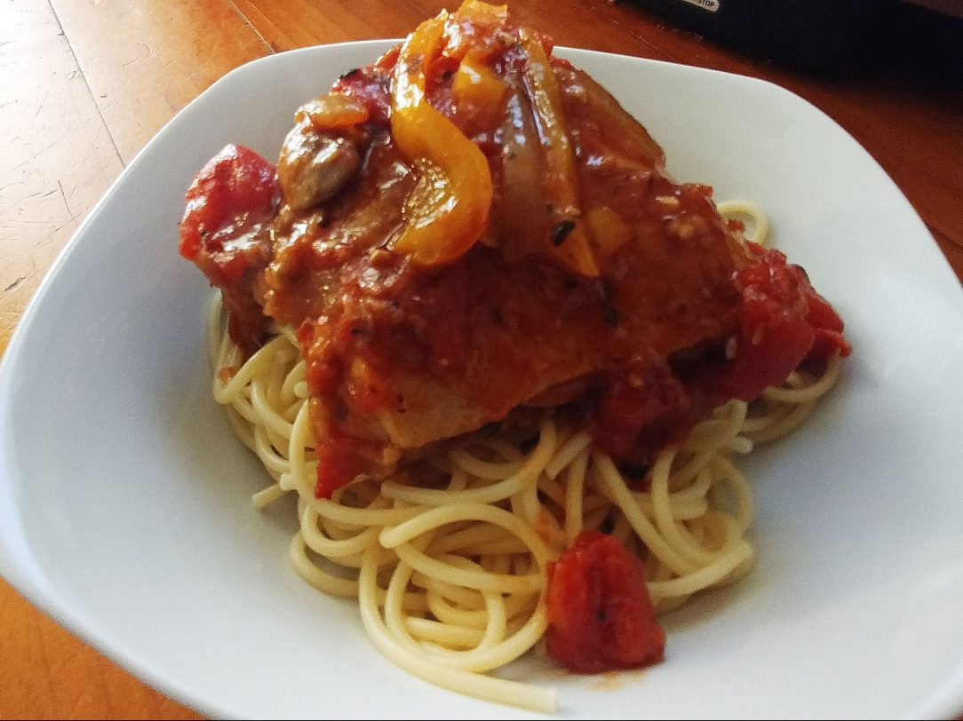 chicken cacciatore over spaghetti in a white plate on a wooden counter