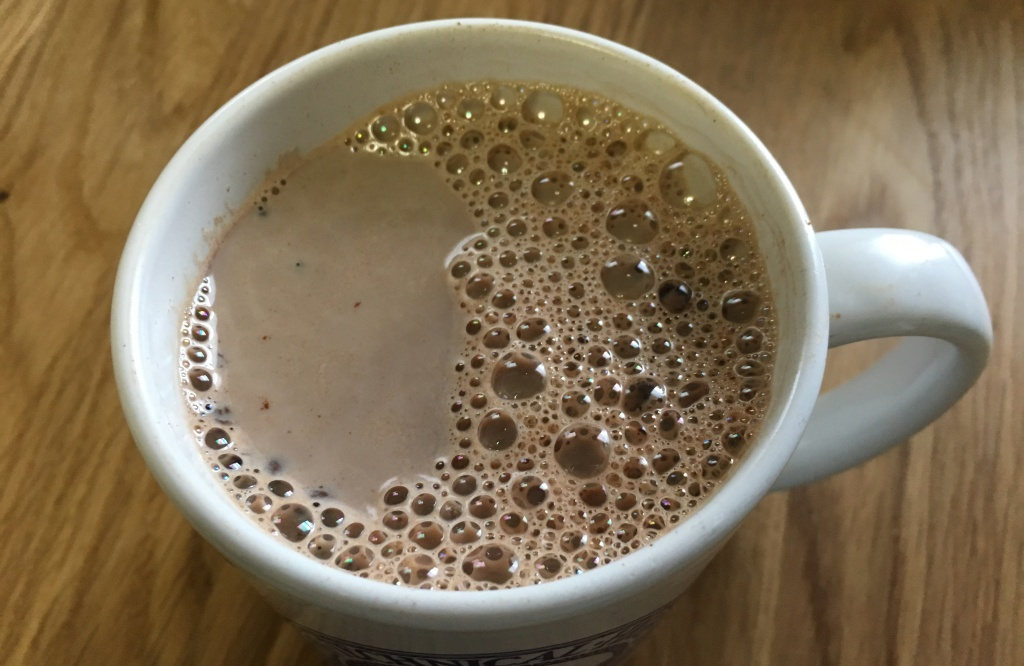 hot chocolate in white mug on wooden surface