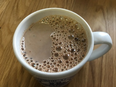 close-up photo of hot chocolate in white mug on wooden surface