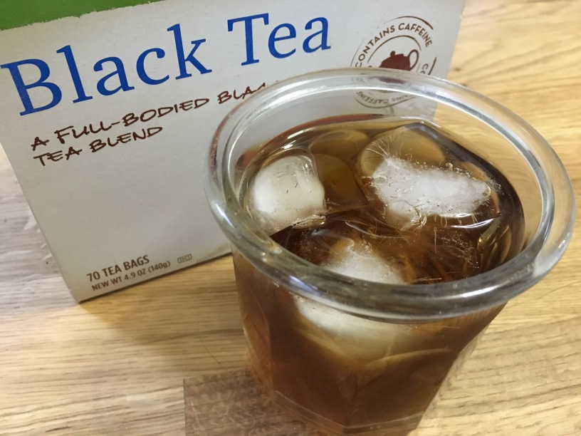 glass of iced tea in front of a box of bagged iced tea on a wooden surface