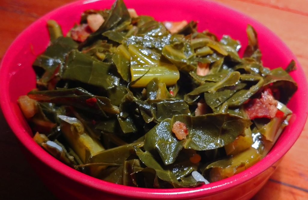 collard greens in a bright red bowl on a wooden surface