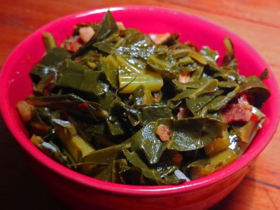 close-up photo of collard greens in a bright red bowl on a wooden surface