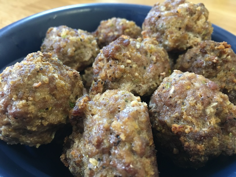 close-up photo of Italian meatballs in a dark blue bowl on a wooden surface