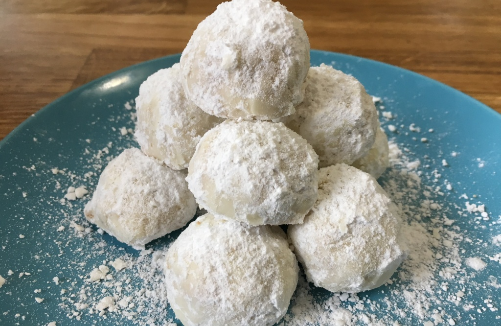 a pyramid of spiced tea cakes cookies surrounded by powdered sugar on a turquoise IKEA FÄRGRIK 8-inch side plate on a wooden surface