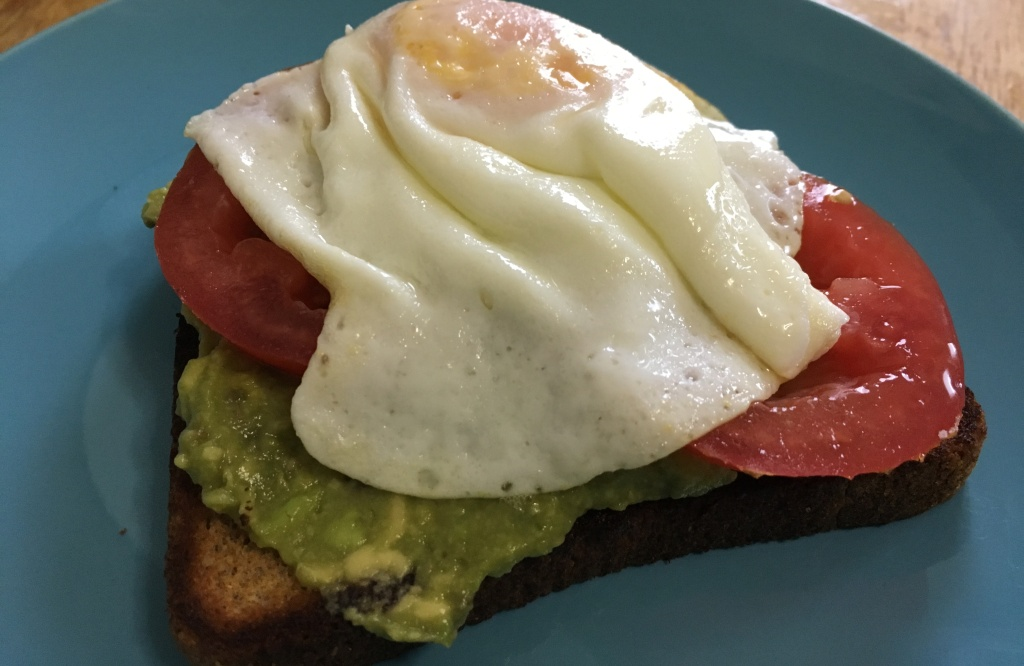 tomato avocado toast with eggs on a turquoise IKEA FÄRGRIK 8-inch side plate on a wooden surface