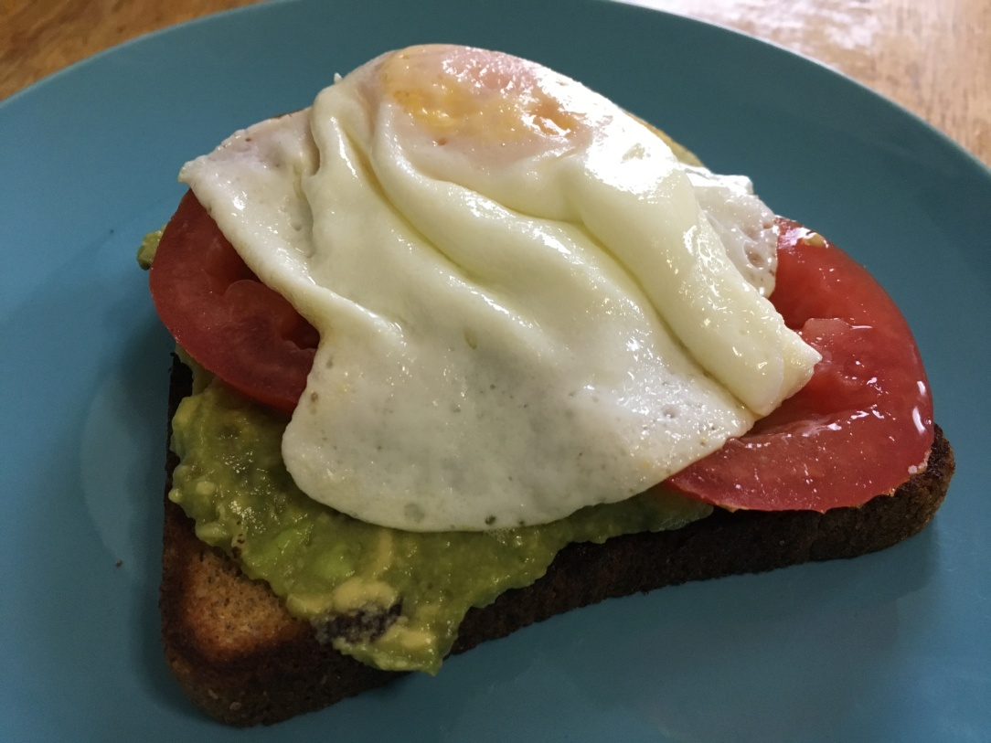 photo of tomato avocado toast with eggs on a turquoise IKEA FÄRGRIK 8-inch side plate on a wooden surface