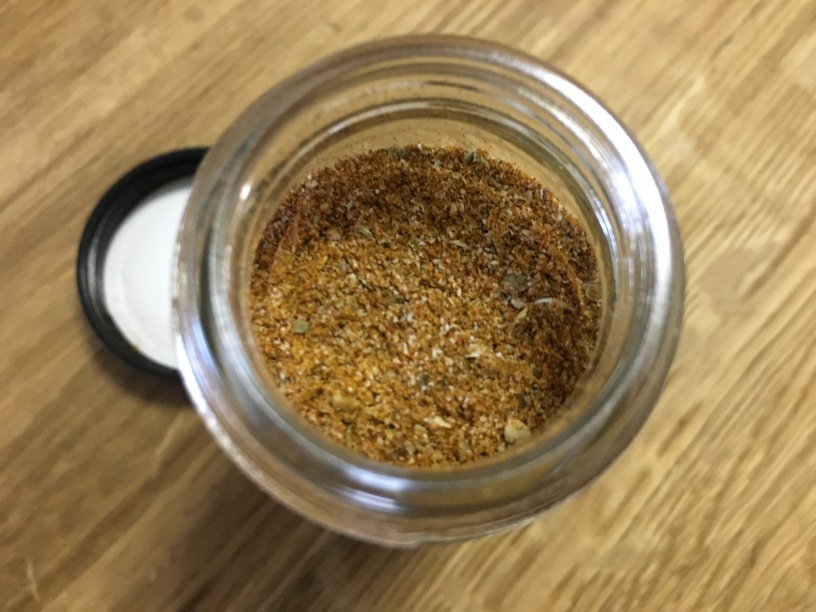 close-up top-down photo of taco seasoning mix in an open glass spice jar on wooden surface
