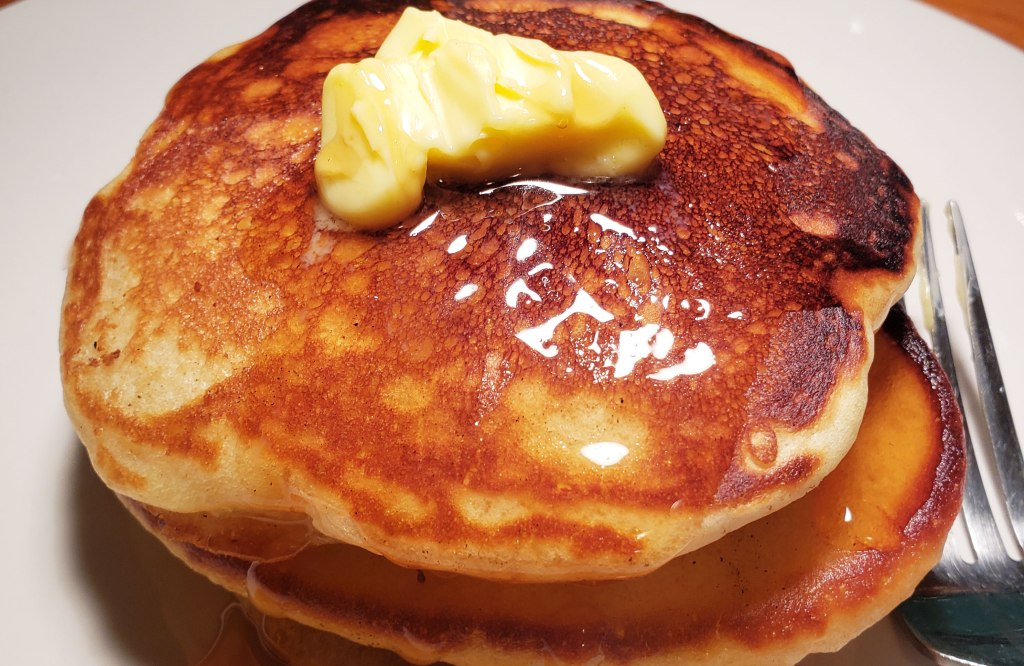 stack of pancakes, topped with butter and syrup