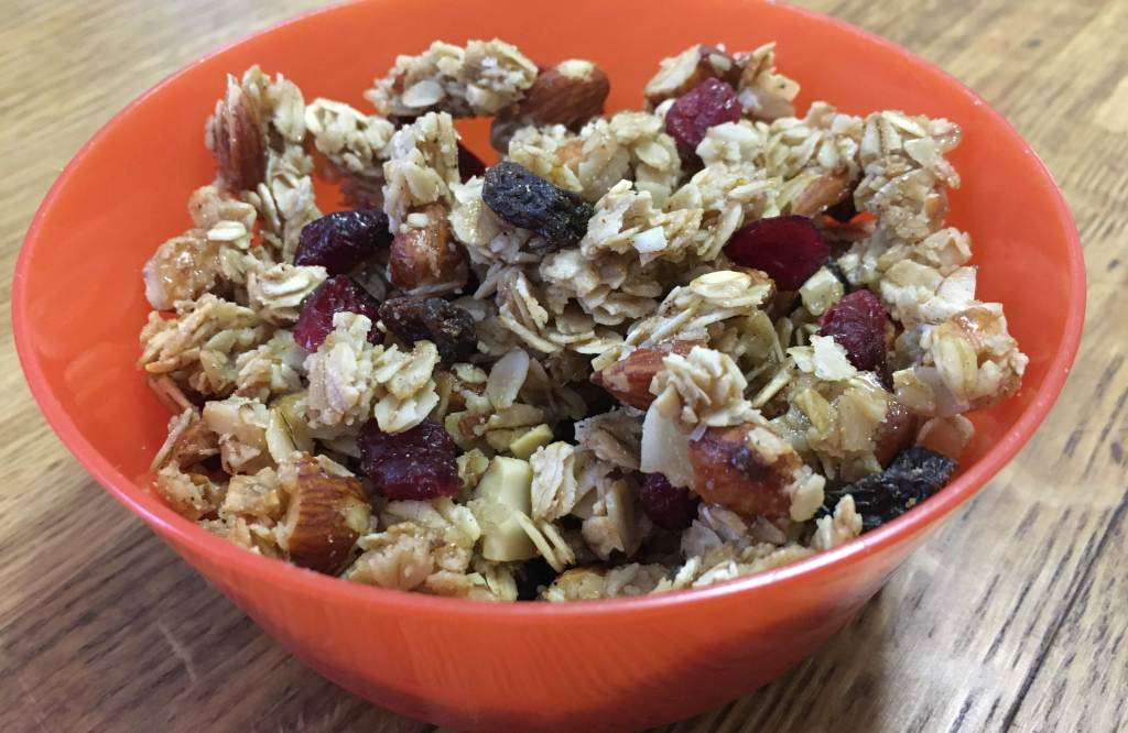 fruit and nut granola in an orange plastic bowl on a wooden surface