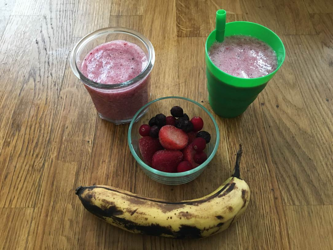 triple berry smoothie in two cups next to a glass bowl of frozen fruit and a ripe banana