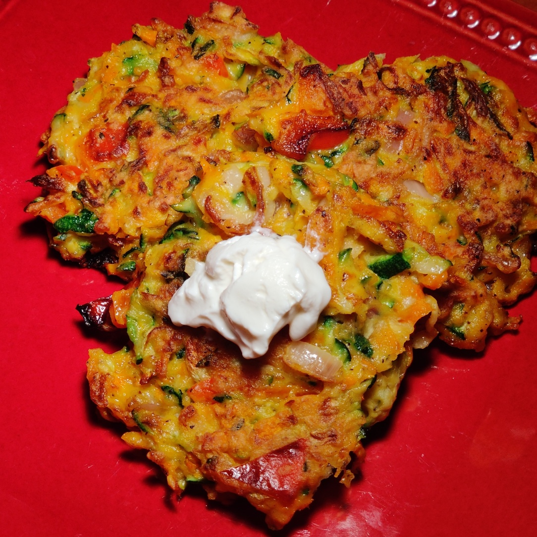 Three colorful vegetable fritters on a red plate. One is topped with a dollop of sour cream.